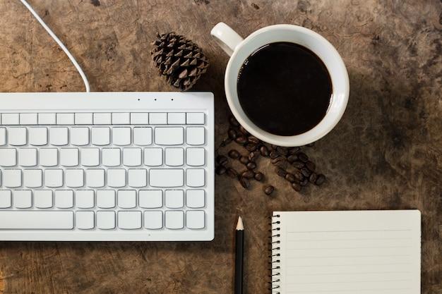 Pracuj z klawiaturą i wypij kubek z kawą na drewnianej podłodze.