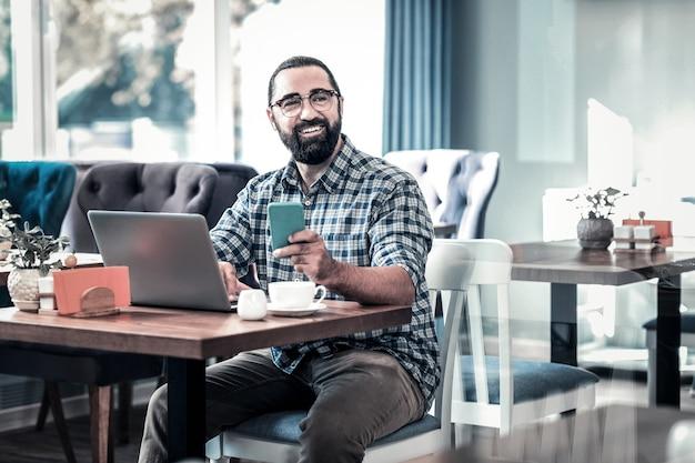 Pracuj zdalnie. sukcesy biznesmen sobie kraciastą koszulę pracy zdalnej, siedząc w restauracji
