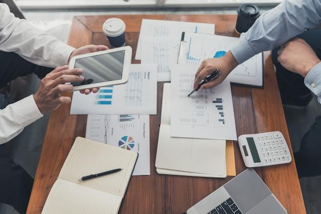 Pracując razem w koncepcji biura, młodzi biznesmeni omawiają sytuację na rynku