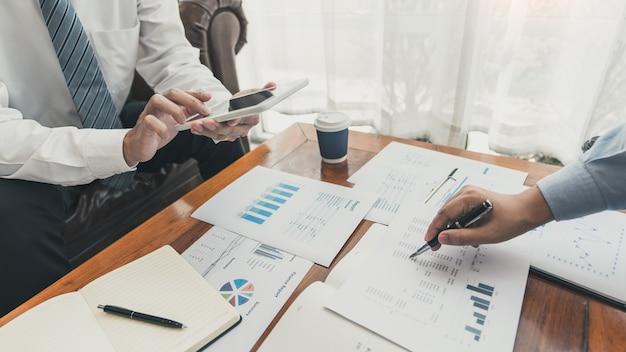 Pracując razem w koncepcji biura, młodzi biznesmeni za pomocą cyfrowego tabletu touchpad