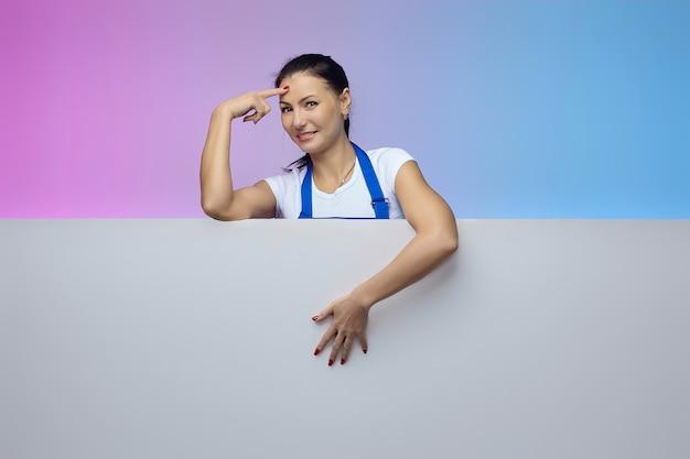 Pracująca dziewczyna w niebieskim fartuchu o azjatyckim wyglądzie pozuje z białym billboardem. koncepcja reklamy