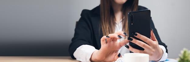 Pracująca kobieta ręce używająca telefonu w biurze