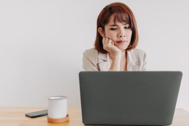 Pracująca kobieta używa laptopa na biurku z białym tłem