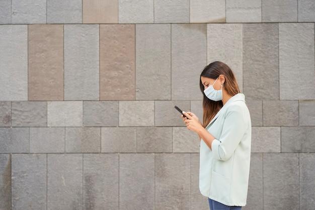 Pracująca kobieta z maską na twarz i za pomocą smartfona. po lewej stronie znajduje się puste miejsce na integrację tekstu.
