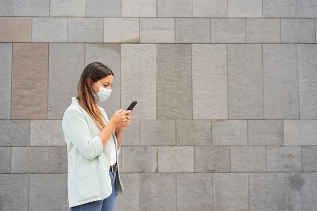 Pracująca kobieta z maską na twarz i za pomocą smartfona