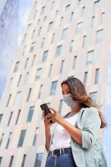 Pracująca kobieta za pomocą smartfona. nosi maskę na pandemię koronawirusa.