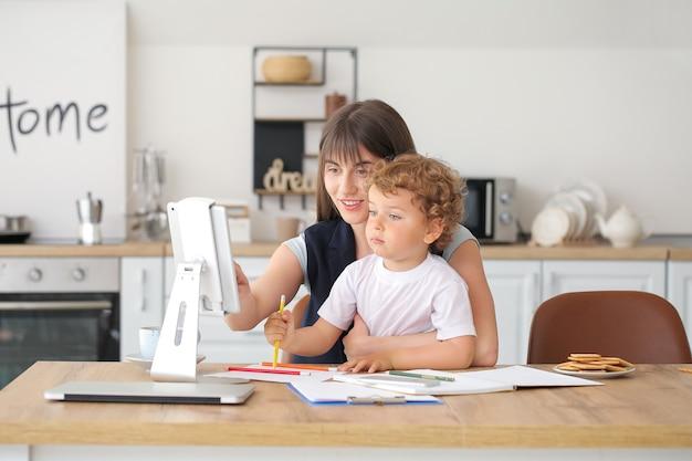 Pracująca mama z małym synkiem w kuchni w domu