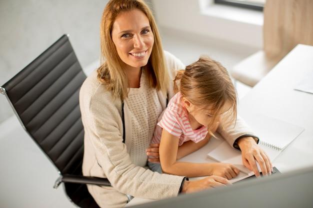 Pracująca matka z uroczą córką w biurze