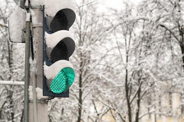 Pracująca sygnalizacja świetlna na ulicy miasta w zimie. sygnalizacja świetlna jest zielona.