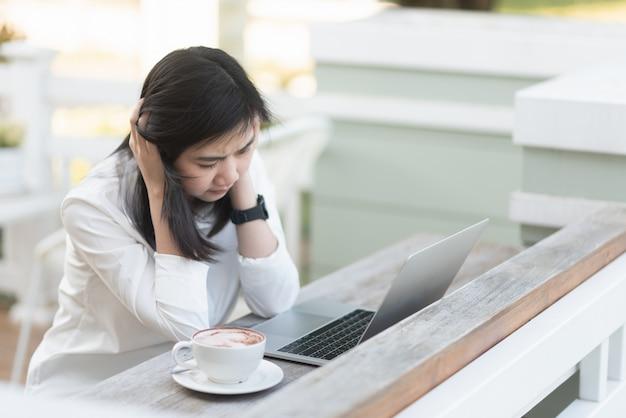 Pracujące kobiety ciężko myśleć i pracuje z laptopem w kawiarni