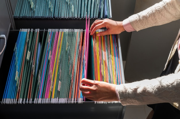 Pracujące kobiety szukają kolorowych akt, posortowanych w szafkach na dokumenty.