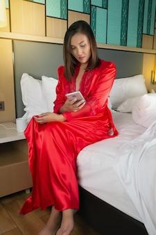 Pracujące kobiety ustawiają alarm, aby obudzić się na telefonie komórkowym w sypialni ośrodka. dziewczyna w czerwonych szatach satynowych za pomocą telefonu komórkowego, siedząc na białym łóżku