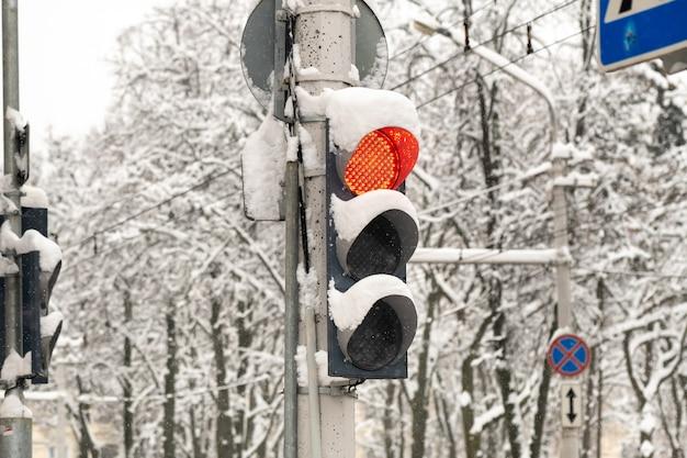 Pracujące światło drogowe na ulicy miejskiej w zimie świeci się czerwone światło sygnalizacji świetlnej