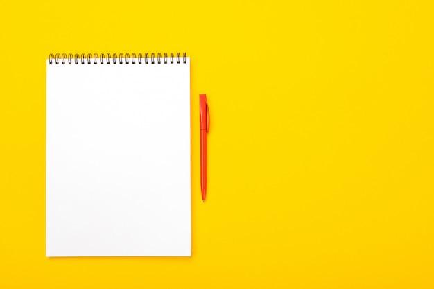 Pracującej przestrzeni stół z notatnikiem i piórem z copyspace odizolowywającym na żółtym tle