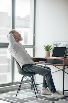 Pracujący . dojrzały, samozatrudniony mężczyzna pracujący w domu i wyglądający na zmęczonego