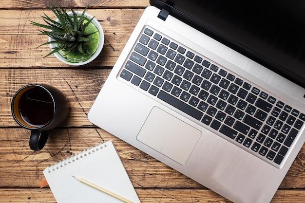 Pracujący drewniany stół w domu lub w biurze. komputerowy laptop kawowy kaktus. płaskie koncepcje świeckich miejsce.