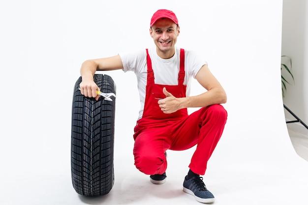Pracujący Mężczyzna W Pełni Wzrostu Trzyma Oponę Na Białym Tle Premium Zdjęcia