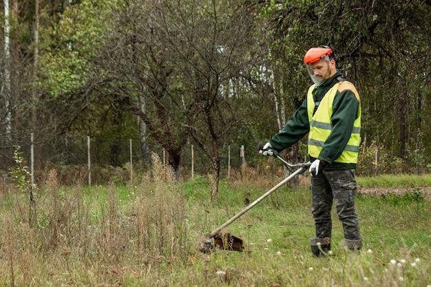 Pracujący mężczyzna w profesjonalnym stroju kosi trawę trymerem