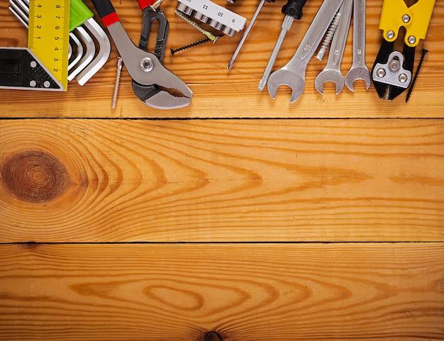 Pracujący narzędzia na drewnianym nieociosanym tle. widok z góry. skopiuj miejsce