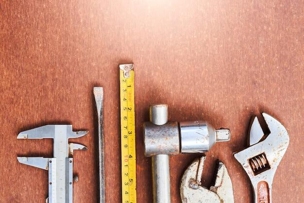 Pracujący narzędzia na drewnianym stołowym tle. widok z góry