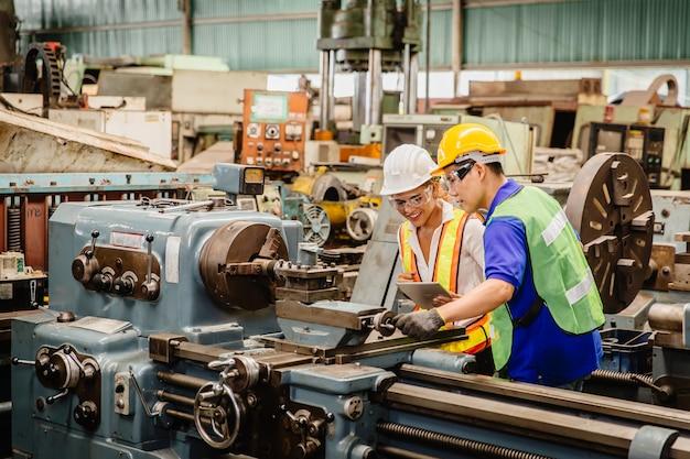 Pracujący razem pracownik rasy mieszanej pomagają sobie nawzajem w pracy w maszynie przemysłu ciężkiego w kombinezonie ochronnym w fabrycznej linii produkcyjnej. inżynier współpracuje z personelem.