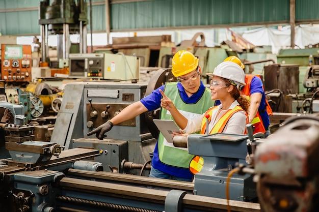 Pracujący razem pracownik rasy mieszanej pomagają sobie nawzajem w pracy w maszynie przemysłu ciężkiego w kombinezonie ochronnym w fabrycznej linii produkcyjnej. inżynier z tabletem współpracuje z personelem zespołu.