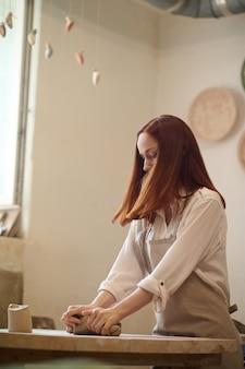 Pracujący. rudy słodki garncarz pracuje w jej warsztacie i wygląda na zaangażowanego