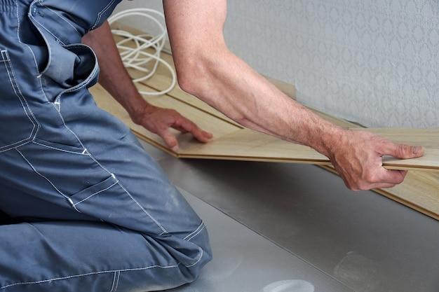 Pracujący stolarz układa w mieszkaniu podłogę laminowaną. pojęcie zawodów pracujących.