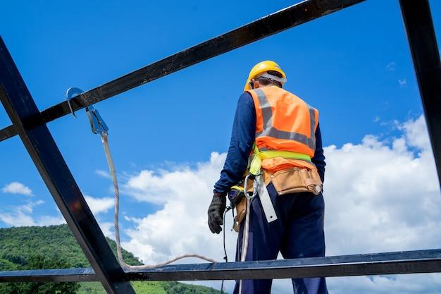 Pracuje na wysokościach. pracownik budowlany ma na sobie uprząż bezpieczeństwa i linię bezpieczeństwa pracującą na budowie na wysokim miejscu.