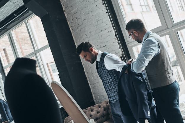 Pracuje nad nowym zamówieniem. młody modny projektant pomagający swojemu klientowi się ubrać