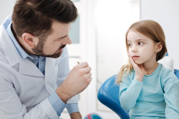 Pracujmy w zespole. przyjemny profesjonalny dentysta dziecięcy mówi małej dziewczynce, że potrzebuje jej pomocy, by znaleźć przyczynę bólu zębów