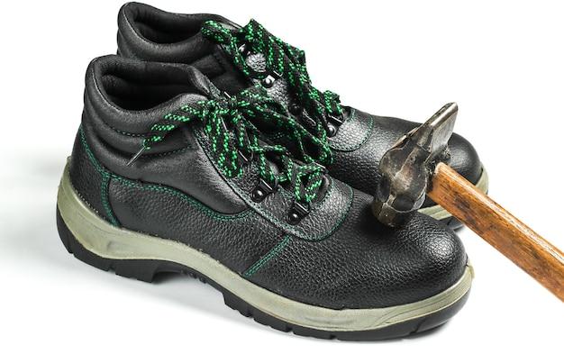 Pracy skórzane buty i młotek na białym tle. kontrola wytrzymałości, bezpieczeństwo pracowników