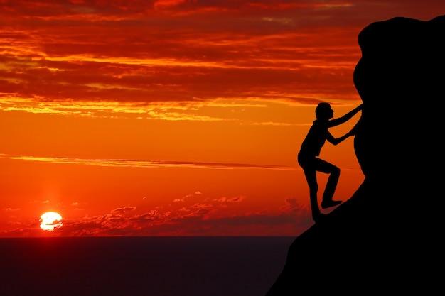 Pracy zespołowej para piesze wycieczki pomagają sobie wzajemnie zaufanie sylwetka pomocy w górach, zachód słońca. praca zespołowa turysta mężczyzna i kobieta, pomagając sobie wzajemnie na szczycie zespołu wspinaczki