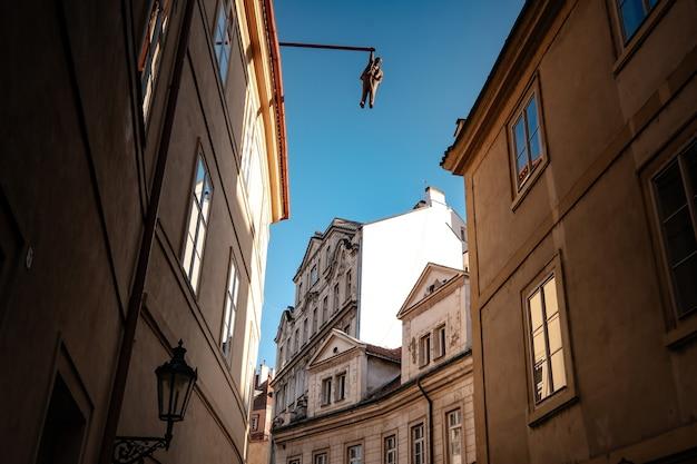 Praga, czechy - 10.08.2019. architektura starego miasta pragi. starożytne budynki, przytulne uliczki. człowiek wychodzić. dzieło davida cerny'ego na starym mieście, przedstawiające zygmunta freuda.