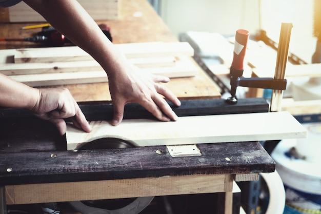 Praktycy stolarzy używają brzeszczotów do cięcia kawałków drewna do montażu i budowy drewnianych stołów dla