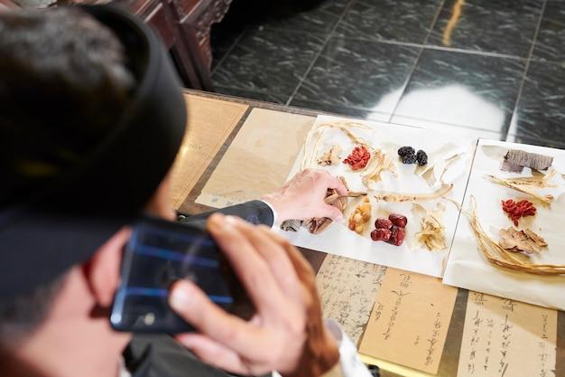 Praktyk medycyny chińskiej wybiera suche korzenie i jagody