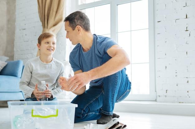 Praktyka czyni mistrza. uroczy młody ojciec uczy swojego syna, jak prawidłowo zgniatać plastikowe butelki przed ich recyklingiem, ćwicząc razem z nim