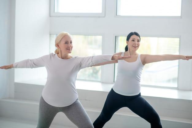 Praktyka jogi. brunetka kobieta i blondynka stojąca w pozie wojownika z rękami równoległymi do podłogi
