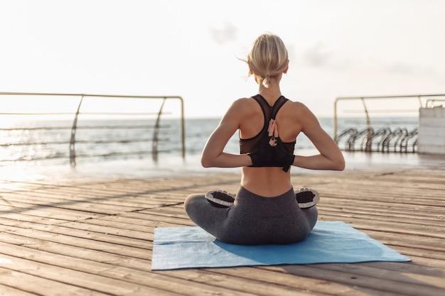 Praktyka jogi o wschodzie słońca młoda joginka robiąca namaste za plecami