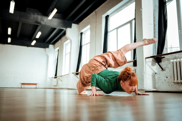 Praktyka jogi. profesjonalna instruktorka jogi z rudymi włosami wyglądająca na skoncentrowaną podczas wykonywania hatha jogi