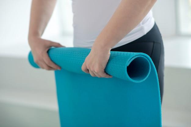 Praktyka jogi. zbliżenie: kobiece dłonie zwijanie dywanik do jogi