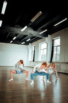 Praktyka taneczna. dwie urocze dziewczyny z pokolenia z wyglądające na skupione podczas ćwiczenia kucania w szkole tańca