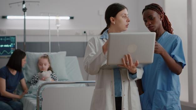 Praktykant kobieta lekarz omawia leczenie choroby regeneracyjnej z afroamerykańską pielęgniarką pediatryczną...