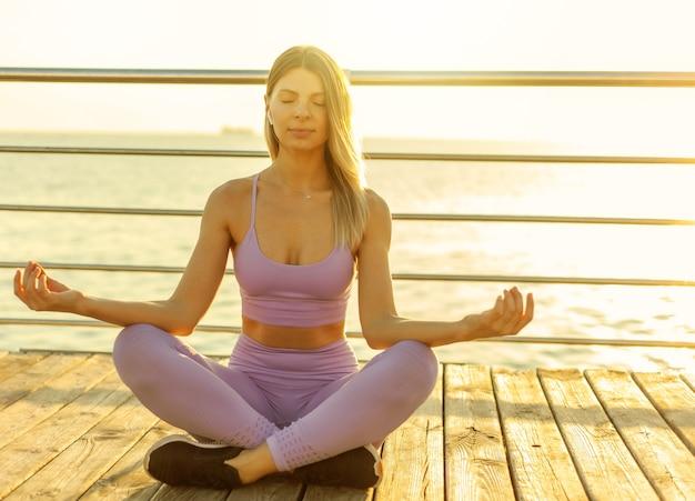 Praktykowanie jogi. medytacja o wschodzie słońca. młoda szczupła kobieta siedzi w pozycji lotosu na plaży. koncepcja zdrowego stylu życia