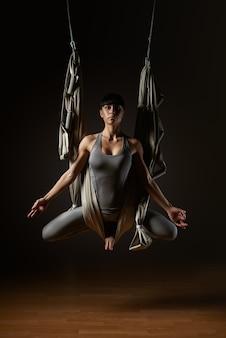 Praktykowanie powietrznej jogi w hamaku