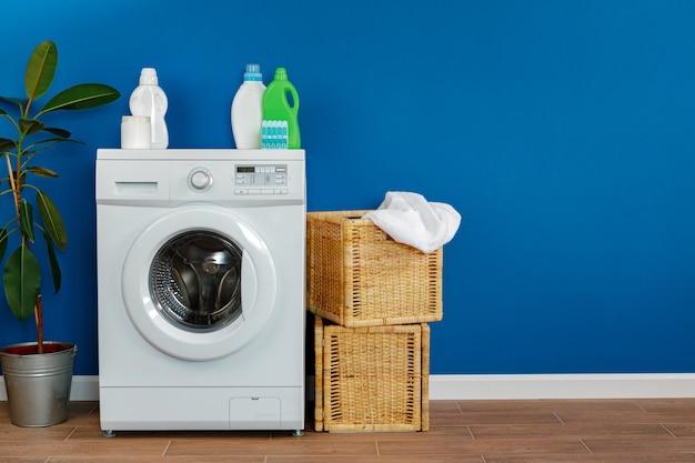 Pralka z praniem na niebieską ścianą