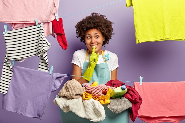Pralnia, czystość i sprzątanie. uradowana gospodyni domowa w fartuchu i gumowych rękawiczkach