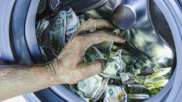 Pranie pieniędzy. korupcja ukrywanie podatków. dolary w bębnie pralki i brudna męska ręka. koncepcja reklamy społecznej.