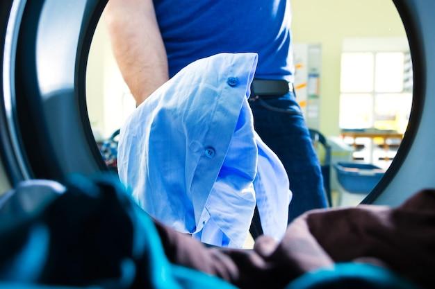Pranie w bębnie pralki, młody mężczyzna wyjmuje kolorowe