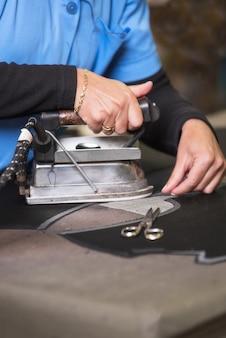Prasowanie tkaniny przez firmę semstress. żelazko krawcowe w warsztacie krawieckim.